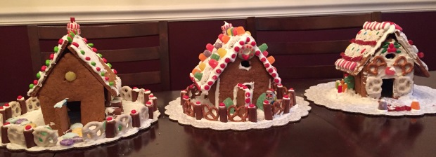 Three lovely decorated gingerbread houses.